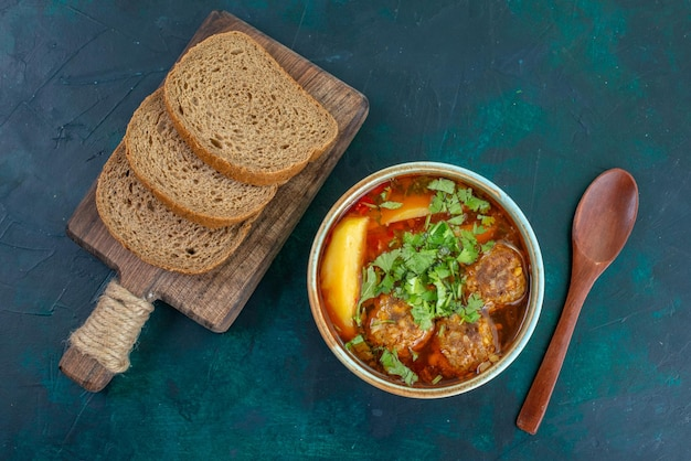 紺色の机の上にミートボールグリーンとパンローフとスライスしたジャガイモのトップビューミートスープ