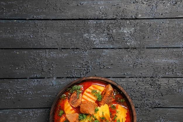 Zuppa di carne vista dall'alto con patate e verdure su sfondo scuro