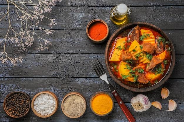 Zuppa di carne vista dall'alto con patate e condimenti sul pavimento scuro