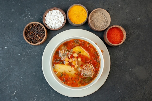 Top view meat soup with seasonings on dark gray background