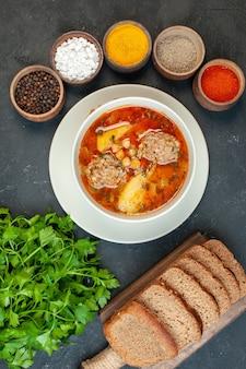 Zuppa di carne vista dall'alto con condimenti su sfondo grigio scuro
