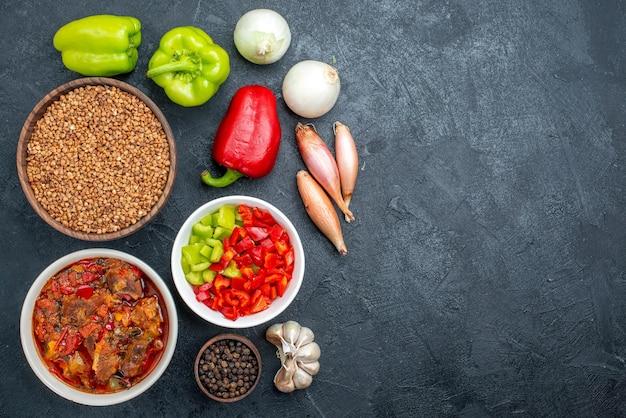 Zuppa di carne vista dall'alto con verdure e grano saraceno crudo su spazio buio dark