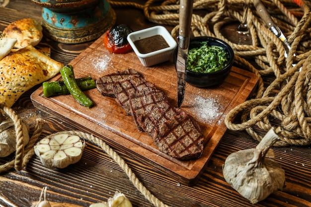 Вид сверху мясной стейк с помидорами на гриле и острым перцем с соусами на подставке с чесноком
