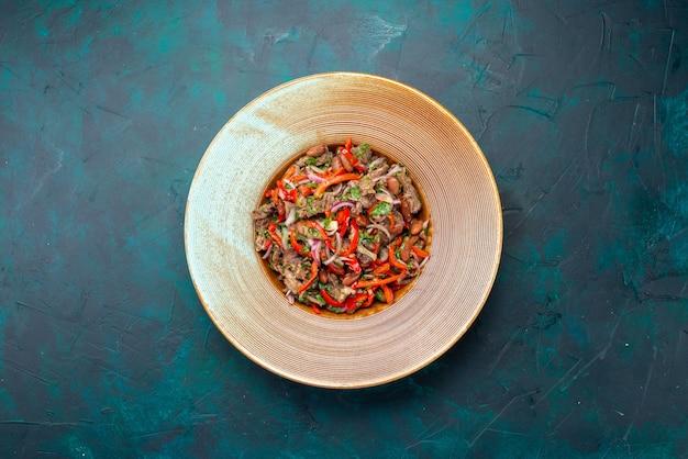 紺色の背景のプレートの内側にスライスされた上面図肉野菜サラダサラダ食品食事野菜成分