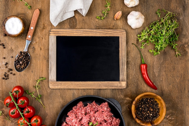 Top view of meat with blackboard and tomatoes