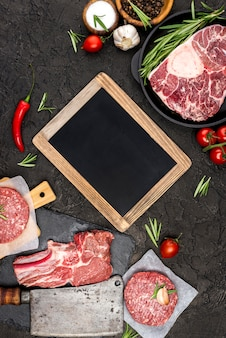 Top view of meat with chili and blackboard