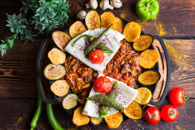 Top view meat with eggplant, tomatoes, potato, pita bread mushrooms and pepper in a round plate horizontal