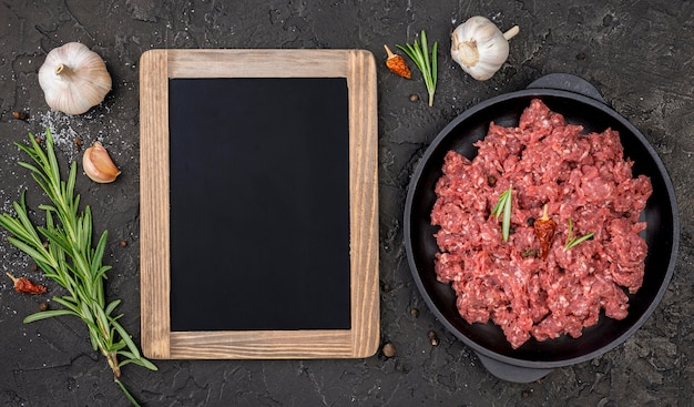 Top view of meat with herbs and blackboard