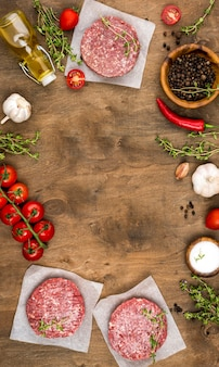 Vista dall'alto di carne con erbe e pomodori