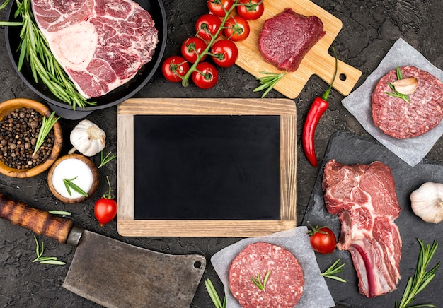 Top view of meat with tomatoes and blackboard