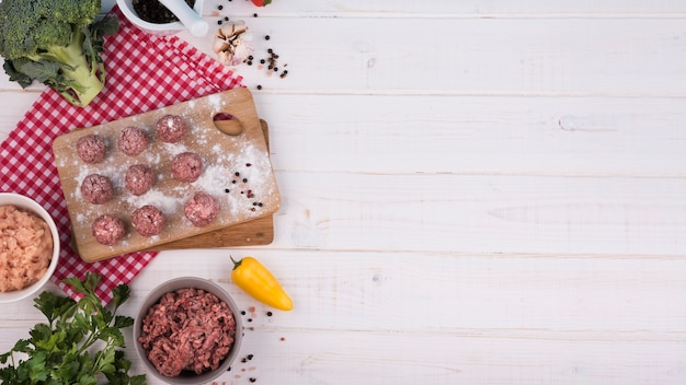 Top view meatballs on wooden board and minced meat with copy space