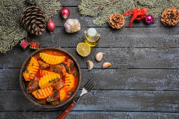 어두운 책상에 채소와 감자가 들어간 상위 뷰 고기 수프 무료 사진