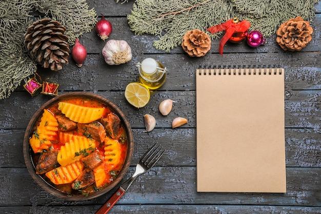 어두운 책상에 채소와 감자가 들어간 상위 뷰 고기 수프