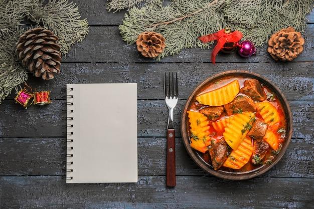 어두운 책상에 감자와 채소가 들어간 상위 뷰 고기 수프