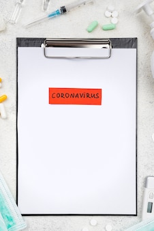 Top view medical desk composition with coronavirus tag