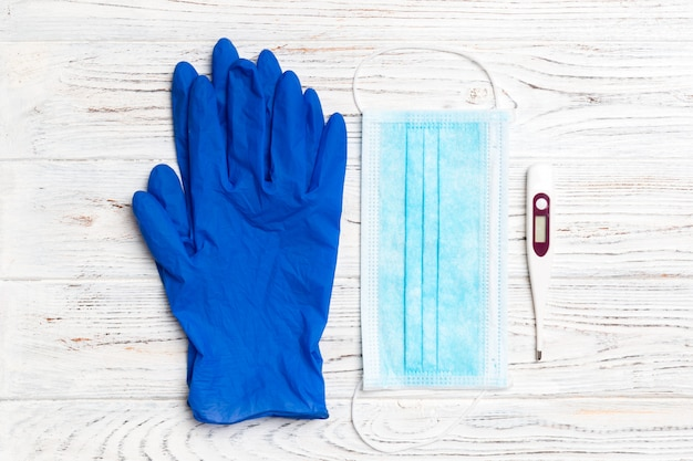Top view of medical gloves, digital thermometer and surgical mask on wooden background with copy space. coronavirus quarantine concept