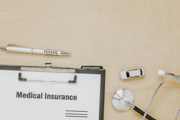 トップビュー医療保険フォーム、聴診器、木製の背景に車。