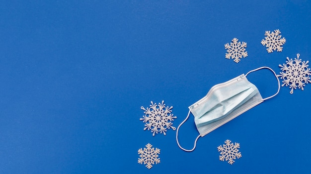 Top view medical mask and snowflakes with copy-space