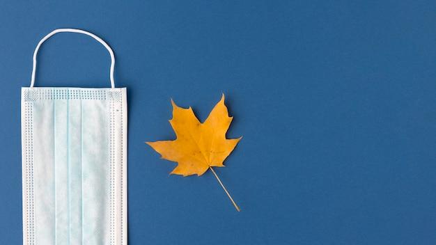 Vista dall'alto della mascherina medica con foglia d'autunno