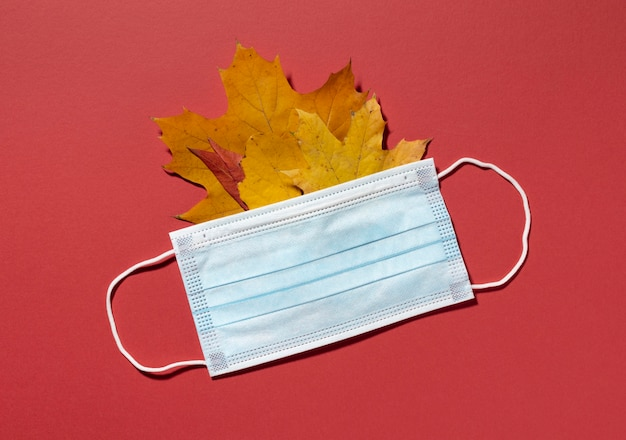 Top view of medical mask with autumn leaves