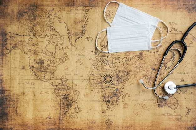 Top view of medical stethoscope and protective face mask on world map background. protection concept