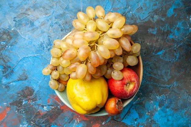 上面図まろやかな果物マルメロリンゴと青の背景のプレート内のブドウ