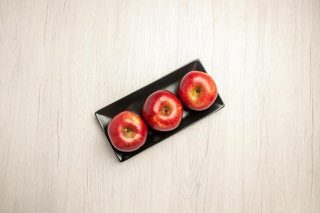 Vista dall'alto mele rosse morbide frutta fresca all'interno di una padella nera sulla scrivania bianca frutta fresca matura dolce colore rosso