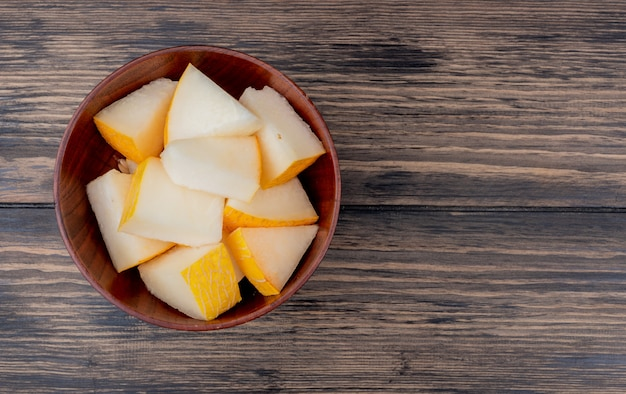 Top view of melon slices in bowl on wooden background with copy space