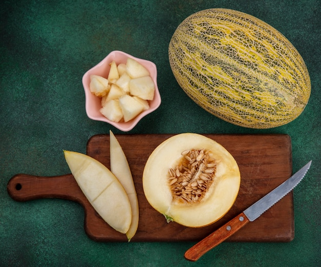 Top view of melon slices on a wooden kitchen board with peels with knife on green surface