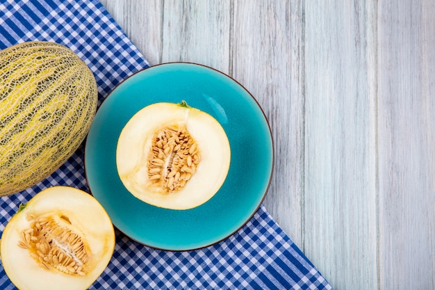 Top view of melons on a blue plate on blue checked tablecloth on grey wooden surface