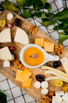 Top view of melted butter with different kinds of cheese grape pieces olives nuts on cutting board on plaid decorated with leaves