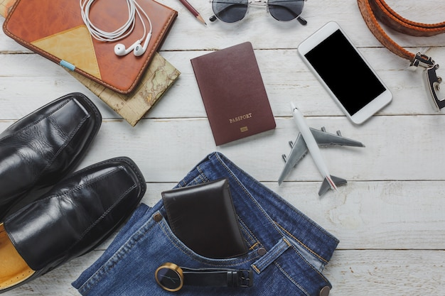 Top view men accessoires to travel concept.white mobile  phone and headphone on wooden background.airplane,hat,passport,watch,sunglasses on wood table.