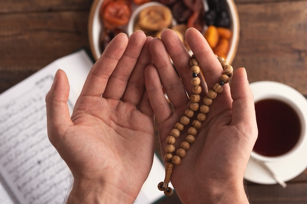 Top view men's hand of prayer with wooden beads in sunlight