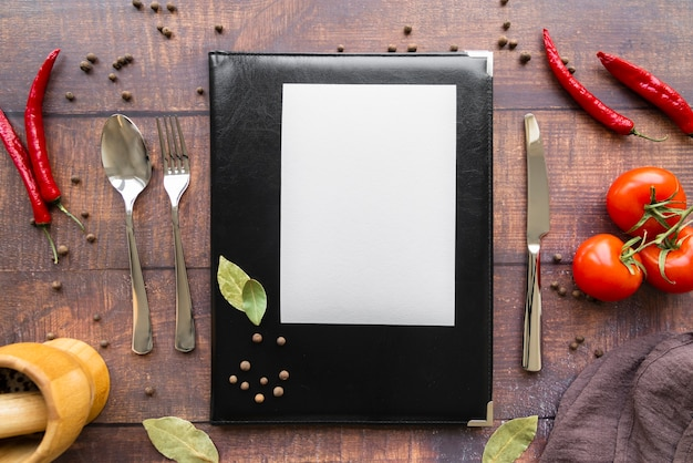 Top view of menu book with chili peppers and cutlery