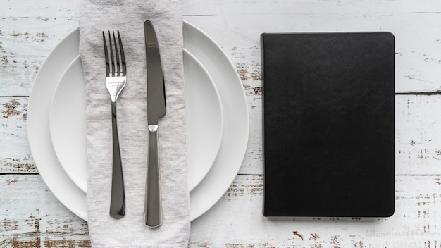 Top view of menu book with plates and cutlery