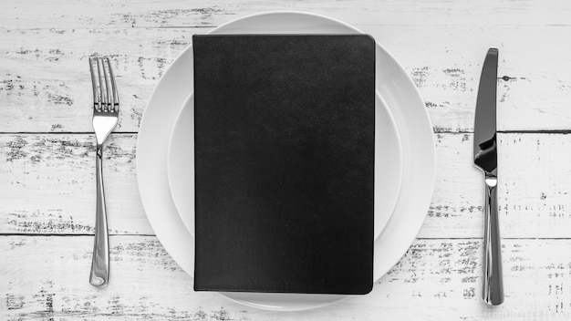 Top view of menu on plate with cutlery