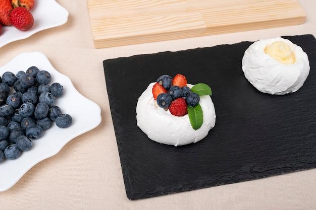 Торт безе вида сверху со свежей клубникой и черникой. торт анны павловой.