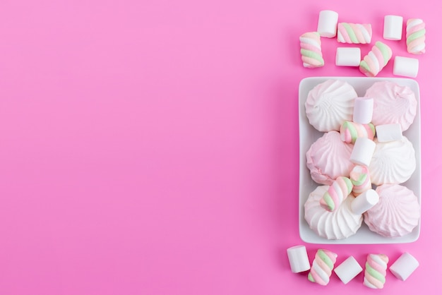 A top view meringues and marshmallow on pink, biscuit cake sugar