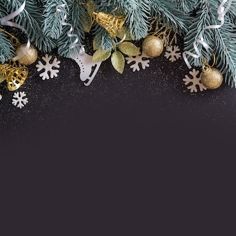 Top view merry christmas black background decorated with christmas tree branches, snowflakes, bells and baubles with copy space