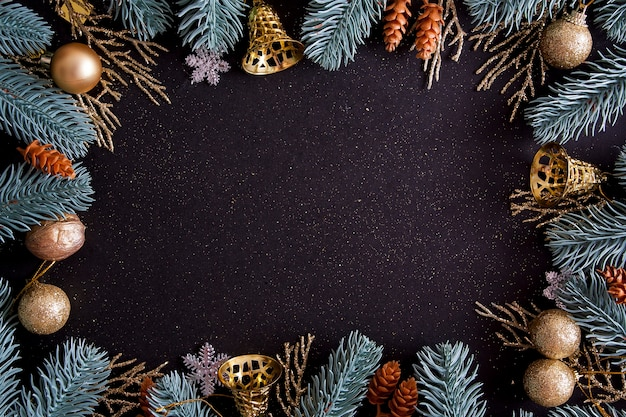 Top view merry christmas black background decorated with happy new year christmas tree branches and baubles with copy space. winter holiday card decoration festive fun concept, flat lay.