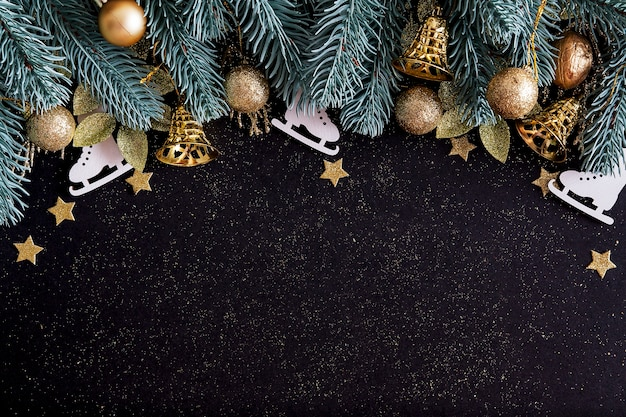 Top view merry christmas black background decorated with happy new year christmas tree branches, stars, bells and baubles with copy space. winter holiday card decoration festive fun concept, flat lay.
