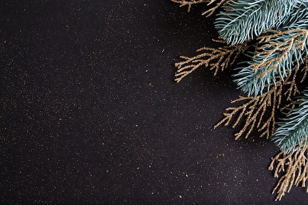 Top view merry christmas black background decorated with happy new year tree branches and glitter with copy space. winter holiday card decoration festive fun concept, flat lay.