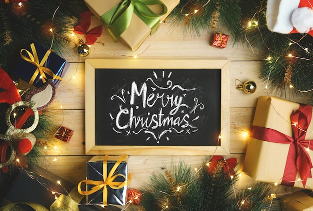 Top view of merry christmas typography on blackboard surrounded by christmas gifts ornament.