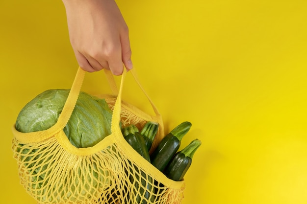 Top view of mesh shopping bag with organic eco green vegetables
