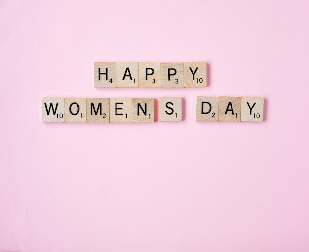 Top view message happy woomans day spelled in wooden blocks on pink background,