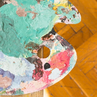 Top view of messy oil paint wooden palette