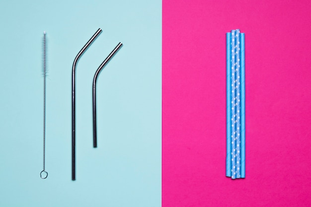 Top view metallic and paper straws on bicolored background
