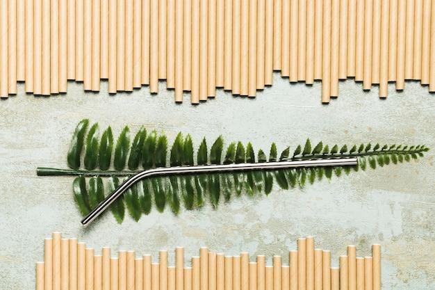 Top view metallic straw on fake leaf