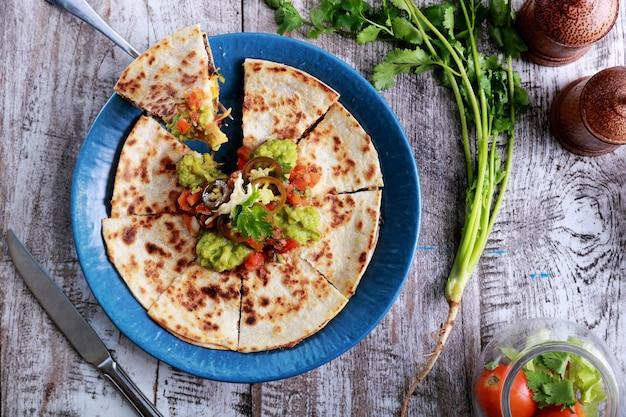Вид сверху кесадилья мексиканской кухни, подаваемой на синей тарелке с гуакамоле, сальсой и халапеньо