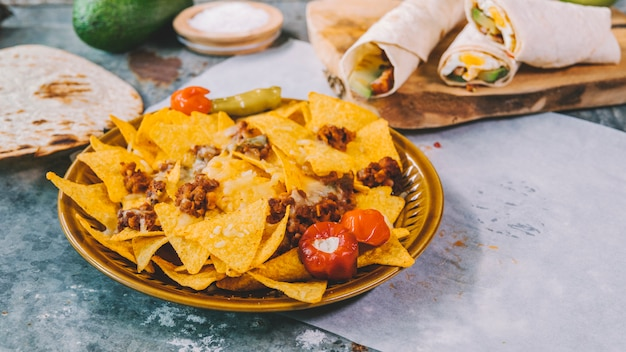 Top view of mexican nachos tortilla chips in bowl with mexican tacos on cutting board